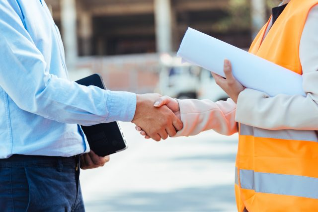 construction worker and business man handshake